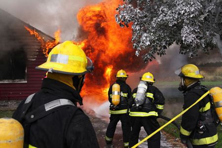incendio casa: Bomberos en el lugar de trabajo en una casa abandonada en llamas