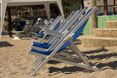 A line of blue arm-chairs on a sandy beach Фото со стока
