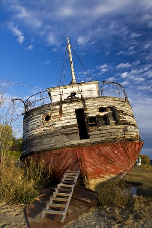 ashore: Photo of an abandoned shpireck left ashore, with dark blue sky