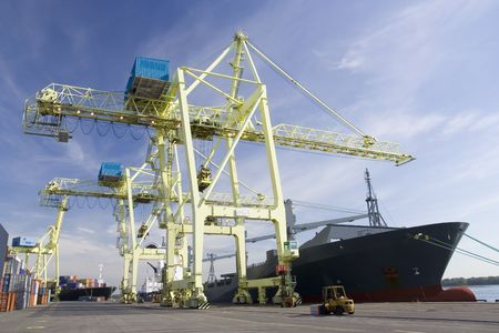 unloading: Giant container crane unloading a ship in a port