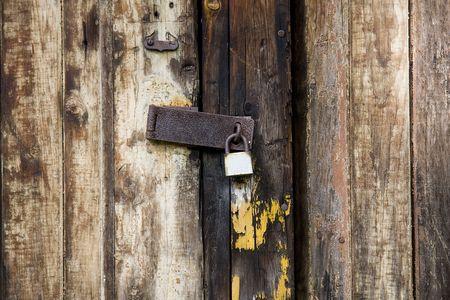 Houten deur of poort vergrendeld met een oude en roestige hangslot