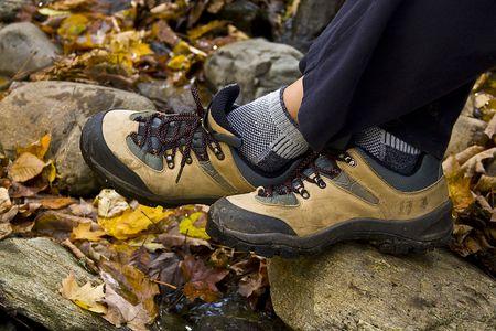 Gezicht op twee voeten dragen van wandelschoenen met herfst bladeren in de achtergrond