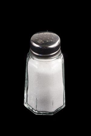 Close-up shot van een zout schudapparaat op zwarte achtergrond