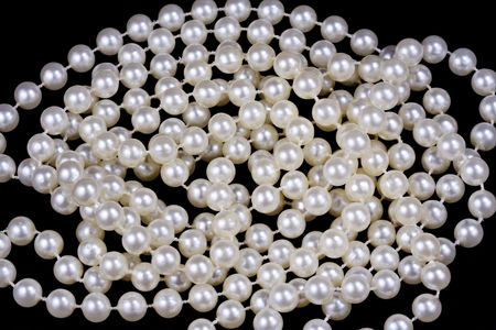 Close up shot of a white pearl necklace over black background