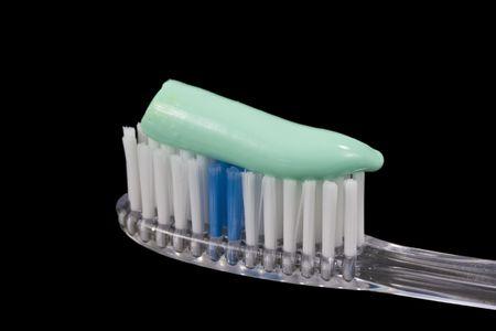 Close up van een tandenborstel met tandpasta op, zwarte achtergrond