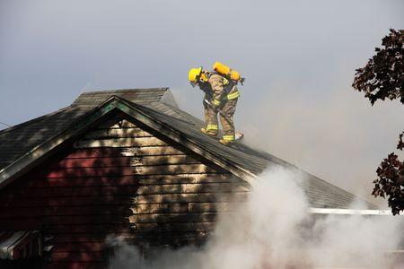 Brandweerman op het dak van een verlaten brandend huis