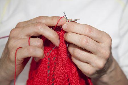 Close-up shot van twee handen breien met rood garen