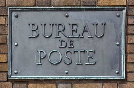 Frans postkantoor teken gemaakt van messing en bouten op een bakstenen muur Stockfoto