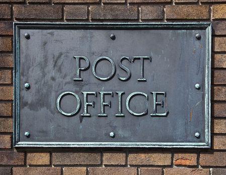 Postkantoor teken gemaakt van messing en bouten op een bakstenen muur