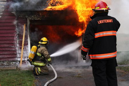 house fire: Abandoned house in flame with firefighters in action Stock Photo