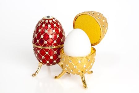 Een rood en een geel jewel paasei met een echte ei binnen de gele één Stockfoto