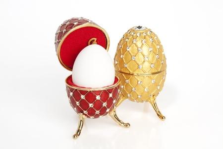 Een rood en een geel jewel paasei met een echte ei in de rode Stockfoto