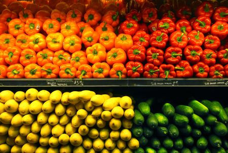 store display: Rows of brightly colored vegetables (bell peppers, squash and cucumbers) in a supermarket. Stock Photo