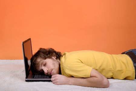 Young man sleeping on the laptop with copy space