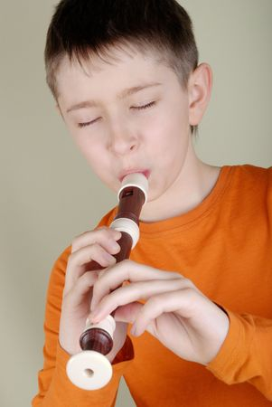 A boy in a bright T-shirt playing the flute