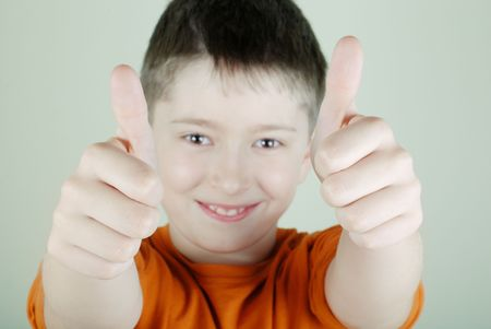thumbup: The smiling boy with thumb-up. Close-up