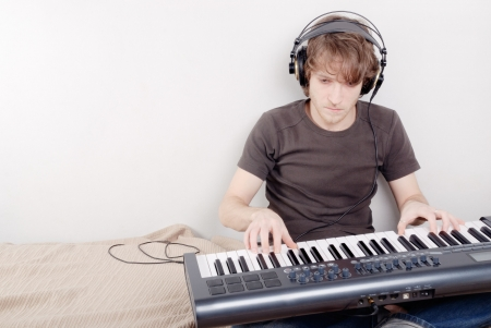 Game process on a MIDI-keyboard, man in headphones Stock Photo
