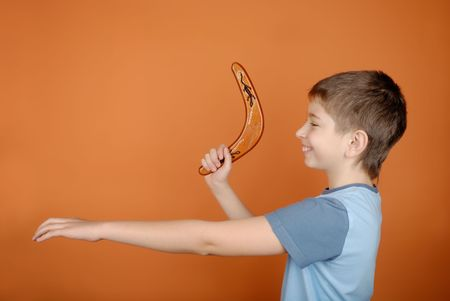Boy with a boomerang on an orange background