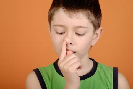 nose picking: Boy is picked in a nose on an orange background