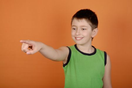 specifying: Smiling boy specifying on... on an orange background