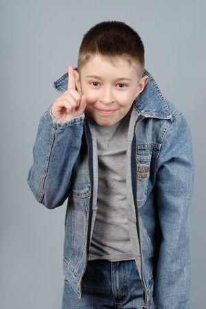 gesticulating: Gesticulating boy pointing a finger upwards