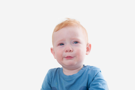Crying redhead boy in blue tank top on the white background