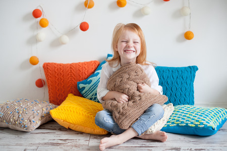 Red head girl among the colorful pillows laughs