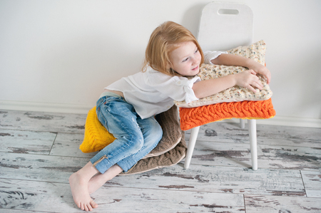 Red-haired girl sitting on crocheted pillows