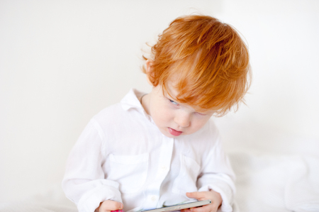 Funny red-haired boy with phone with copyspace Stock Photo