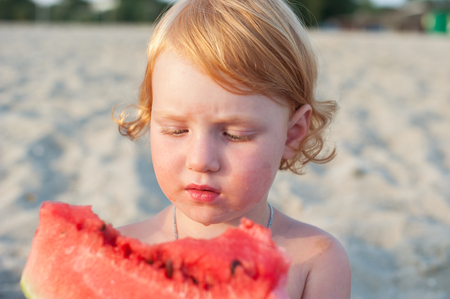 The girl is eating a watermelon and all messed up