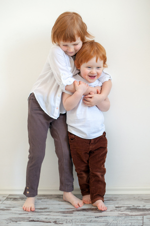 Brother and sister tightly embrace