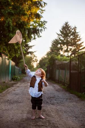 A boy with a net on a country road Reklamní fotografie