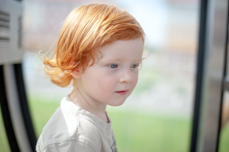 Redhead child thinks and looks into the void