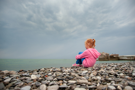 Girl sitting on a rocky beach with knees