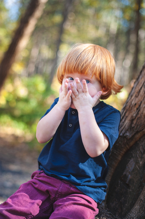 Red-haired boy covers his face with his hands