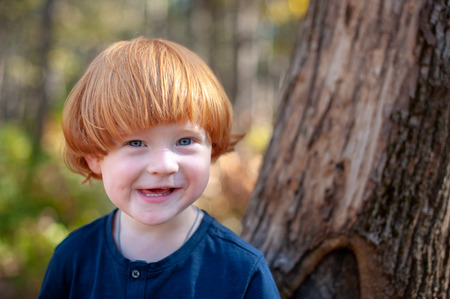Red-haired boy smiles funny