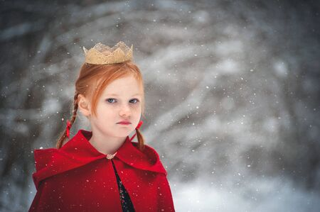 Girl in a red coat with a gold crown on her head Stock Photo