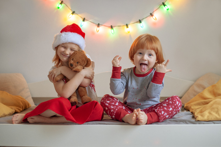 Brother and sister sit on a bed in a Christmas setting