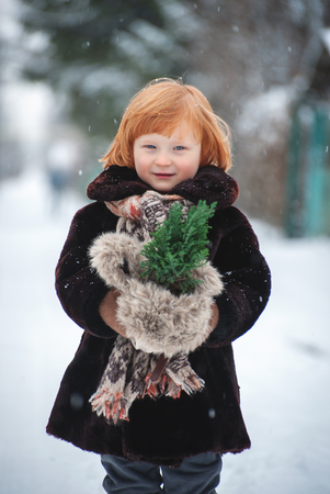 A boy with long red hair holds a small Christmas tree in the snow Banco de Imagens