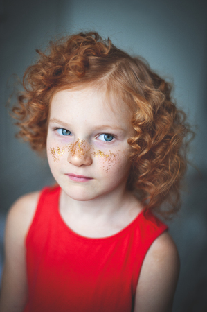 Curly red-haired girl in a red dress and glitter on the nose Banco de Imagens