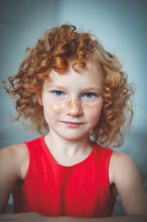 Curly red-haired girl in a red dress and glitter on the nose Stock Photo