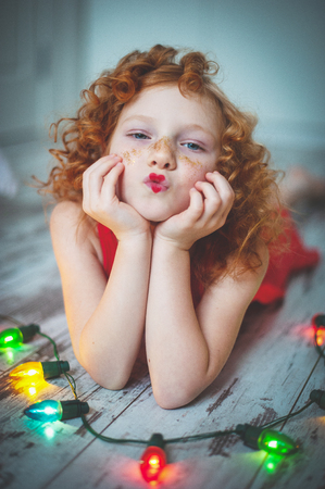 Curly red-haired girl in a red dress sends a kiss