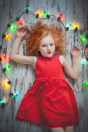 Curly red-haired girl in a red dress lying with a garland
