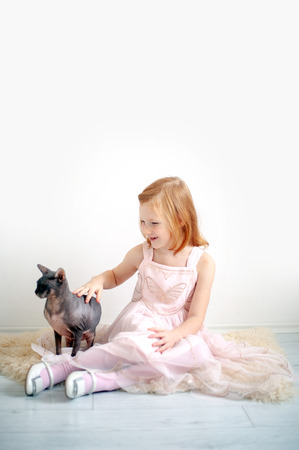 A girl in a pink dress with a bald cat Banco de Imagens