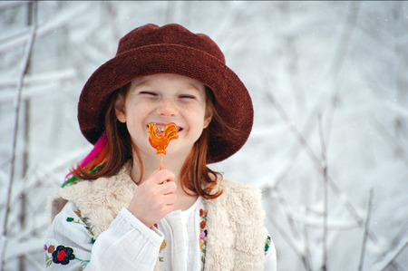 Girl in a hat with candy on a stick