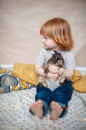 Red-haired child with a rabbit in his arms