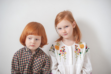 Red-haired children, brother and sister are sitting nearby