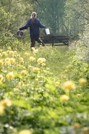 A girl running through the flowers with two water buckets photo