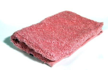laundered: A pink wash cloth isolated on white
