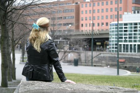 viewed from behind: Young woman viewed from behind sitting in a park. Stock Photo